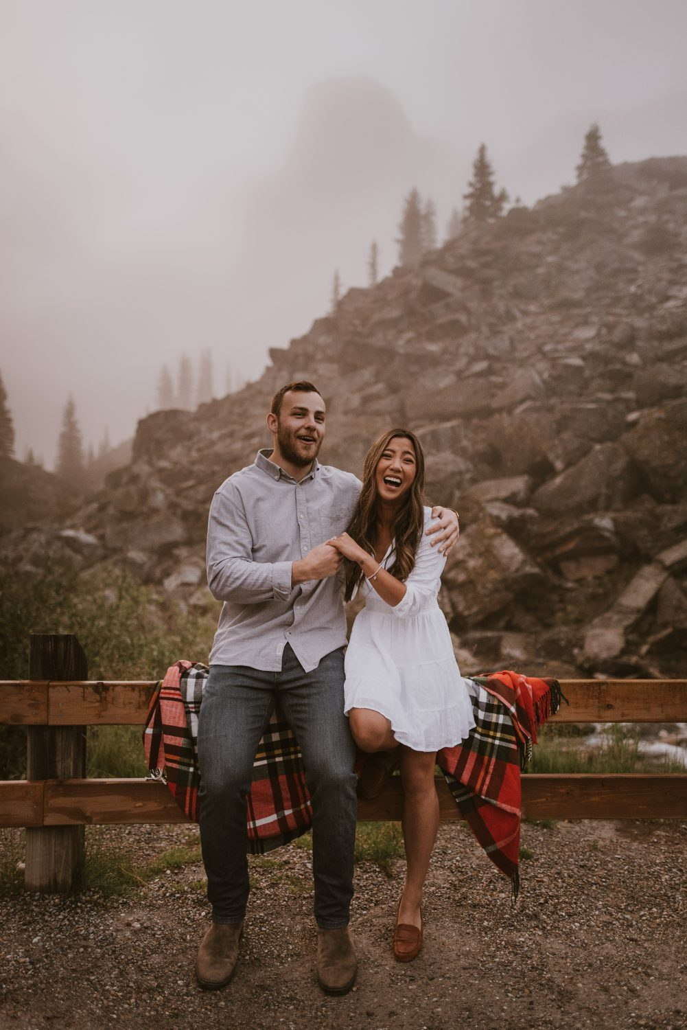 Couple sitting on a fence with mountains in the background